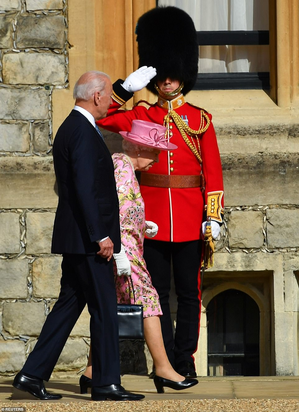 The Queen and US President Joe Biden are saluted as they walk on the grounds of Windsor Castle on June 13