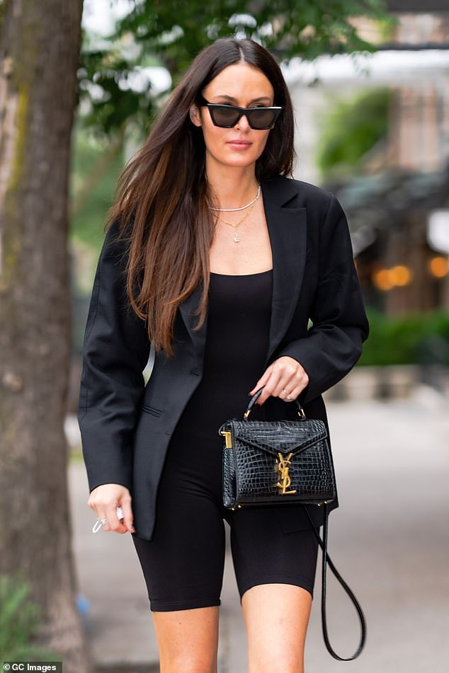 Sleek: The Australian model accessorised her look with a black YSL handbag and heeled leather boots