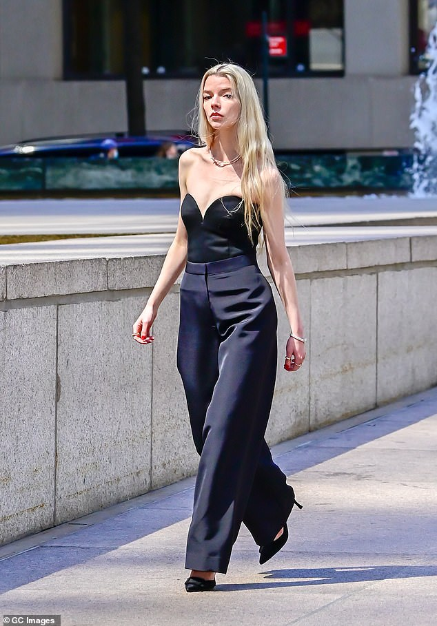 So chic in black: The beauty had on a top with a sweetheart neckline and tailored trousers