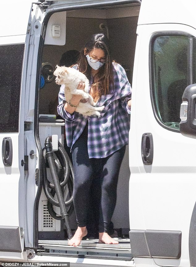 Low key beauty:The bombshell was dressed down in leggings and an oversized plaid shirt with a face mask and eye glasses