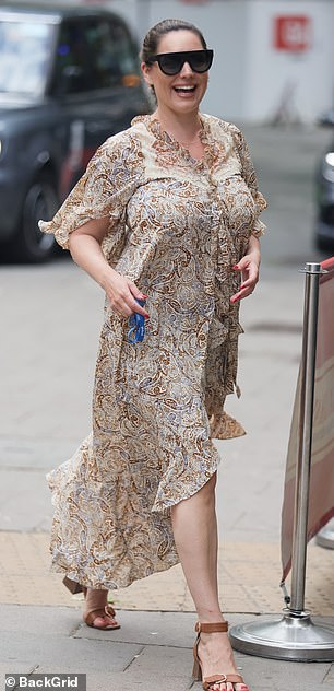 Summery: Kelly embraced the warmer weather in the flowing cream and brown dress, which she paired with black sunglasses
