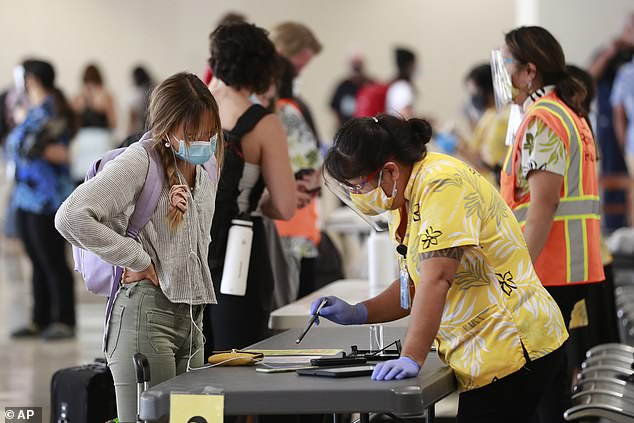 A fully vaccinated resident in Hawaii has tested positive for the Indian Delta coronavirus variant, health officials revealed on Monday. Pictured:A traveler is assisted by a state official at the Daniel K. Inouye International Airport in Honolulu, Oahu