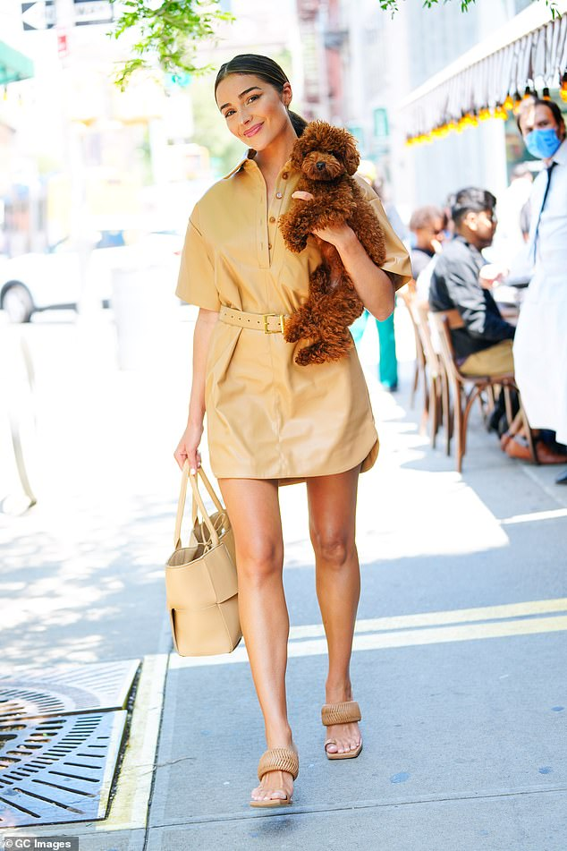 Puppy love: Olivia Culpo posted a big smile on her face as she carried her beloved puppy for a lunch outing in New York on Tuesday
