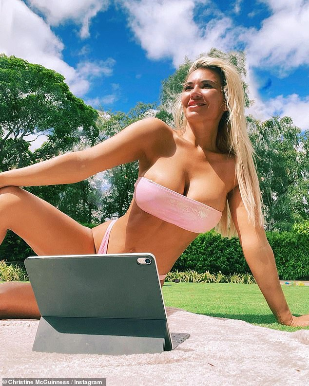 'Office today': Christine McGuinness showed off a busty display in a pink two-piece on Wednesday as she basked in the sun in Cheshire and worked on her iPad
