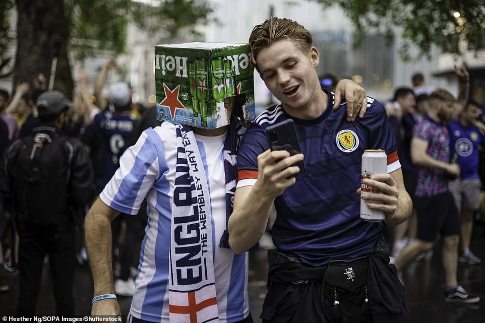 A Scotland supporter speaks with an England supporter last night wearing a beer box on his head before the Uefa clash