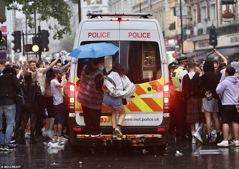 Two people ride the back of a Metropolitan Police van in Leicester Square last night ahead of the Euro 2020 clash
