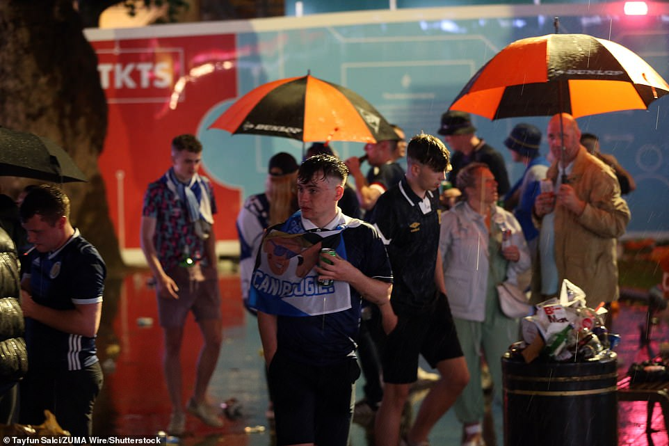 Fans were draped in Scotland flags and some hid under umbrellas to shelter from the rain as they gathered last night