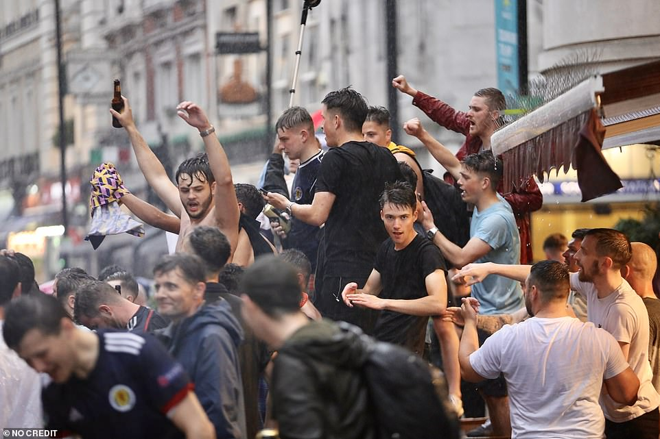 Scotland football fans party in the pouring rain in Leicester Square, central London ahead of the Uefa clash yesterday