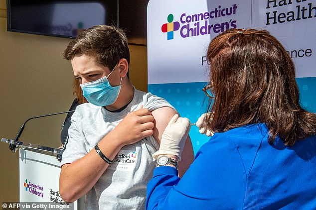 So far, 484 cases have been reported out of 90.6 million doses, which means the risk occurs in 0.000534% of young adults. Pictured: Max Zito, age 13, is inoculated by Nurse Karen Pagliaro at Hartford Healthcares mass vaccination center at the Connecticut Convention Center in Hartford, Connecticut, May 13