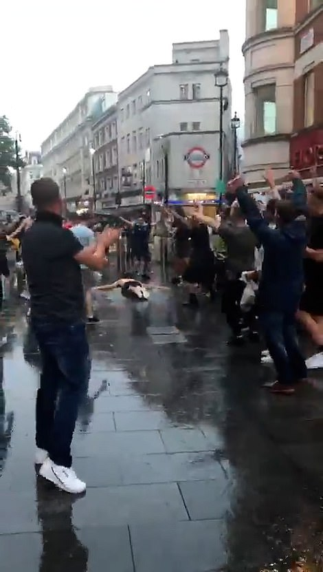 A topless fan has a run up then slides on the wet pavement to the delight of the gathered supporters during the crazy scenes ahead of the highly-anticipated clash