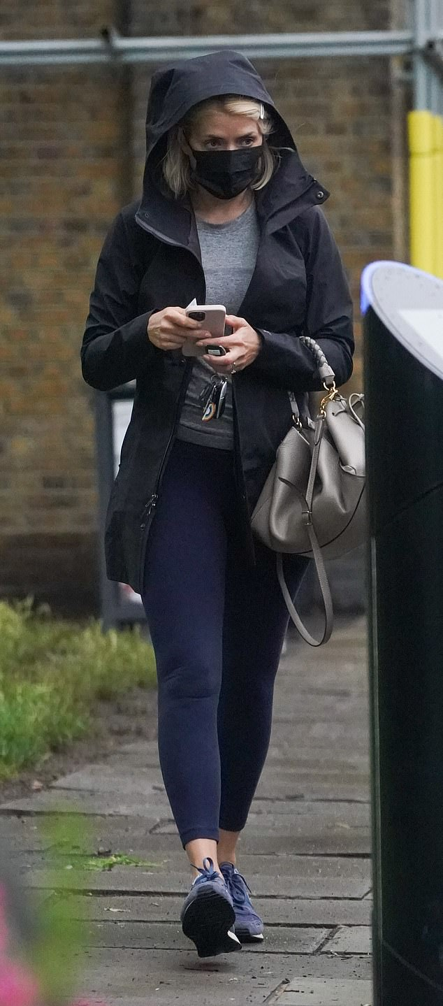 Stormy weather: Holly Willoughby looked ready as she braved bad London weather in gym leggings and a black hoodie on Friday