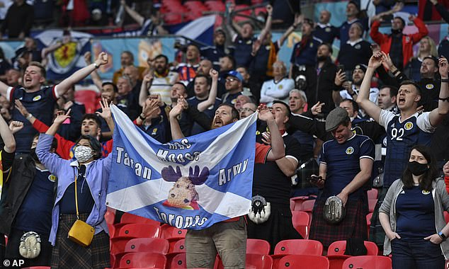 Scotland's players opted against taking the knee before their Euro 2020 opener against the Czech Republic on Monday, with both teams instead deciding to stand. Pictured, Scotland fans