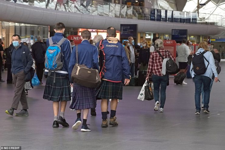 Three supporters wearing kilts make their way through Kings Cross station this morning before the long journey home