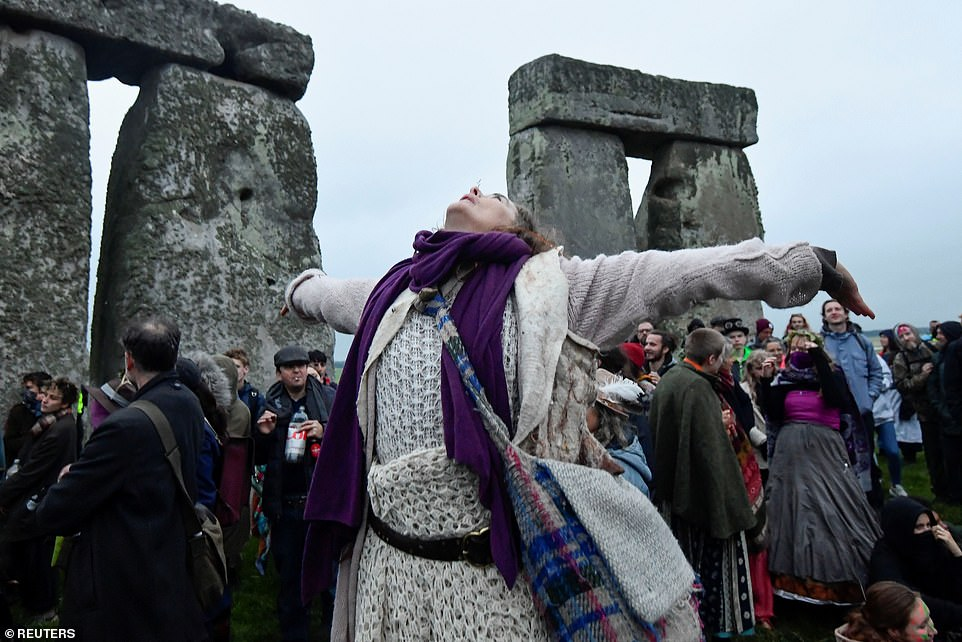 A person looks up as she attends the celebration of the Summer Solstice at Stonehenge