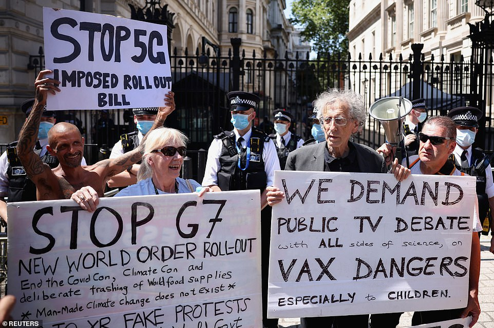 Piers Corbyn (right)held an anti-vaxxer banner alongside protesters calling climate change a 'con' and complaining about the 'New World Order'