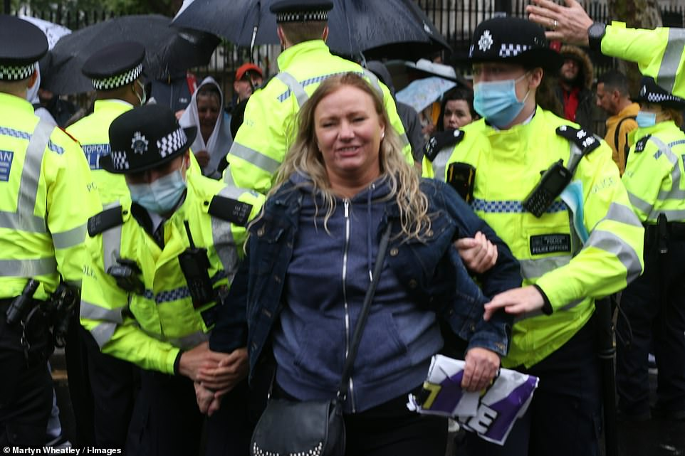 A woman is held by police as covid deniers and other conspiracy theorists groups stage an anti-lockdown protest in Westminster
