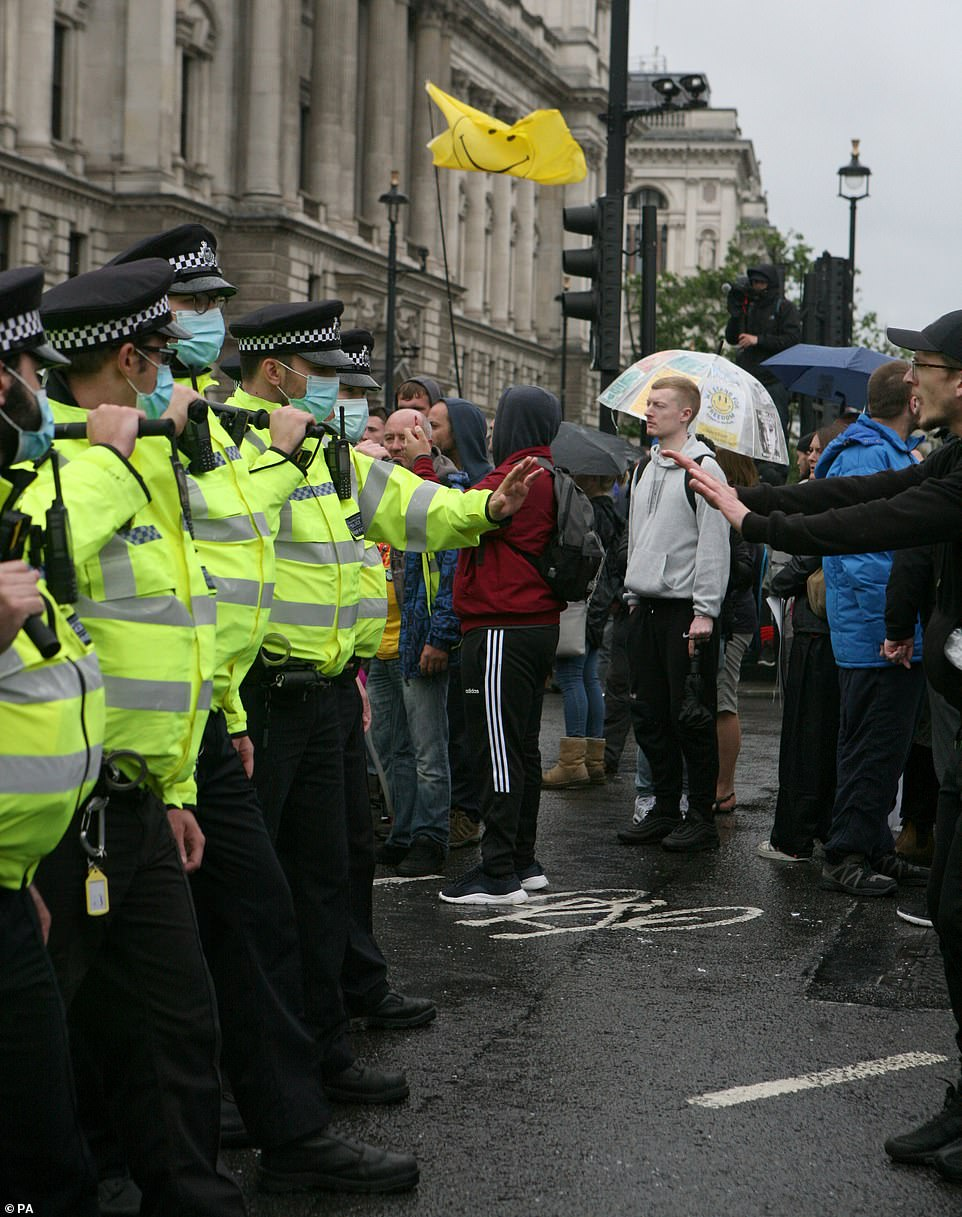 Police officers and protesters at an anti-lockdown protest in Parliament Square, London