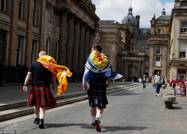 Scotland fans are draped in flags while walking through Glasgow in the sunshine this afternoon ahead of the match tonight