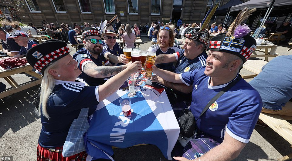 Cheers to that: Fans in Glasgow raise a glass in the hopes their boys will make history against Croatia tonight