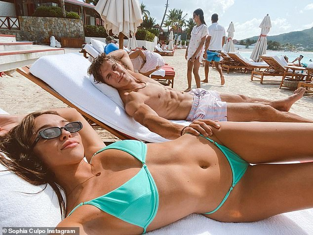 Not a care in the world: The two were seen sitting on lounge chairs side by side as they seemed to be a close couple. Here he has a hand on her hip