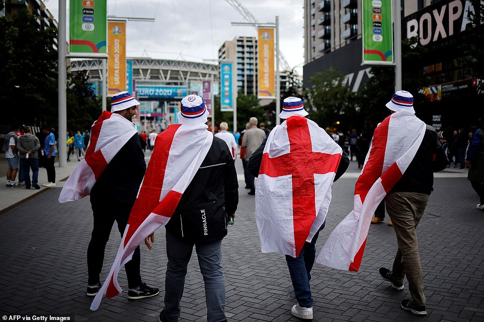 Three Lions fans dressed in bucket hats and draped in England fans walk up Wembley walk towards the stadium ahead of tonight's match