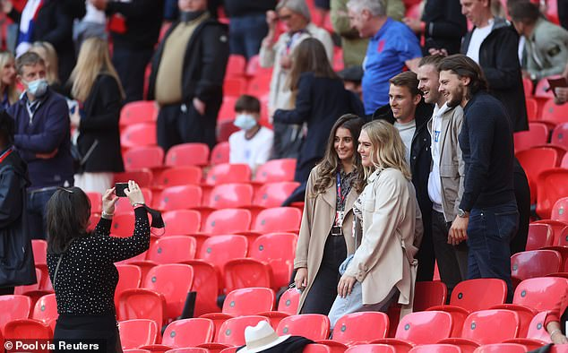 Katie Goodland, who wore her shoulder-length blonde hair loose, opted for a relaxed beige shirt and light blue jeans as she joined family to cheer on her husband. Pictured, posing for photos at the match