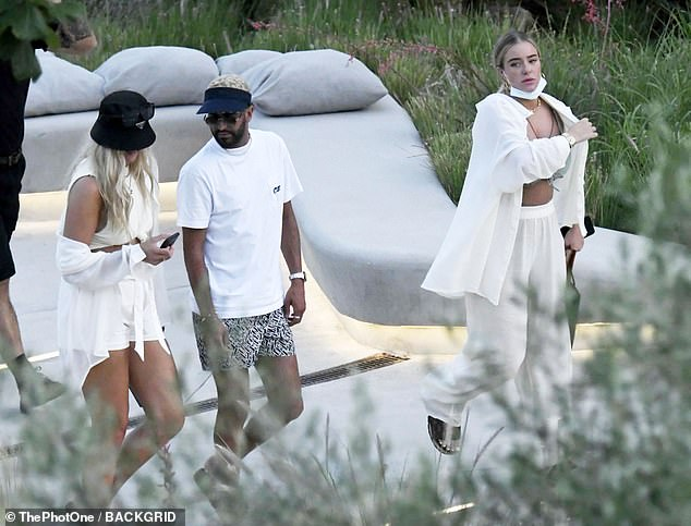 Soaking up the sun: She carried a Louis Vuitton tote bag in her hand as she made her way to the sun lounger, while Riyad chatted to a pal