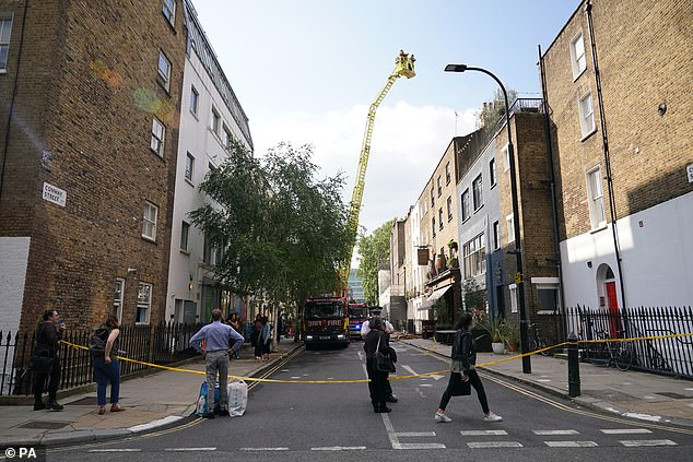Several members of the public stopped to have a look from a cordon while the firefighters worked at salvaging the building