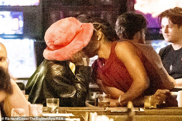 Locking lips: The couple kissed as they relaxed by the bar