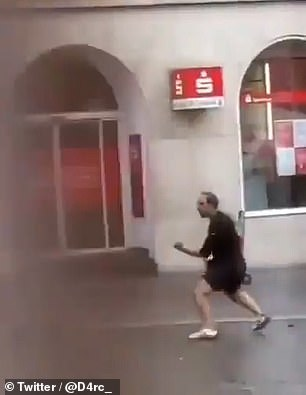 The second man, armed with a bag, attempts to scare off the knifeman