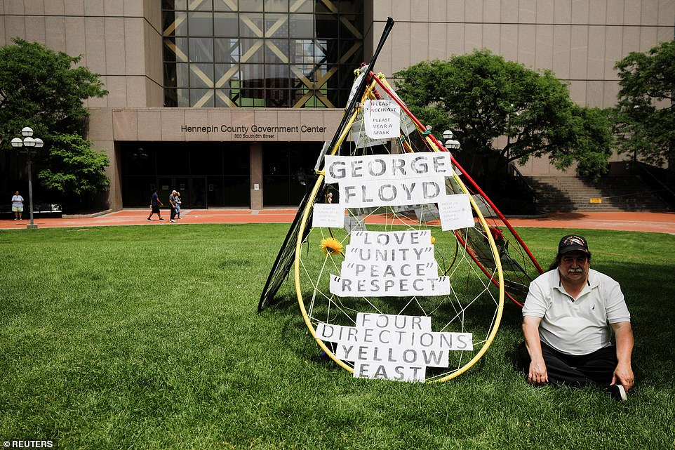 A person listens to live stream outside Hennepin County Government Center ahead of the sentence being pronounced