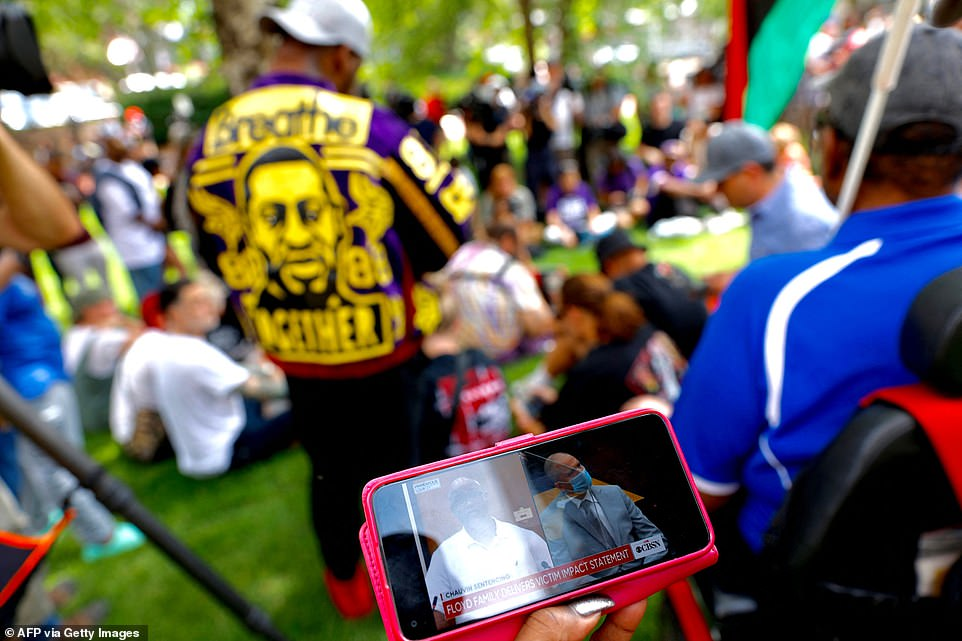 People watch the sentencing hearing of former Minneapolis Police officer Derek Chauvin outside the Hennepin County Government Center