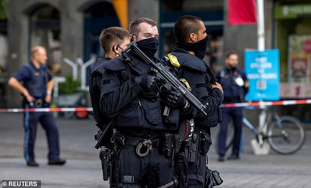 The knifeman killed at least three people and wounded at least five others in the street rampage. Pictured: Armed police secure the cordoned-off area in the city centre in Germany