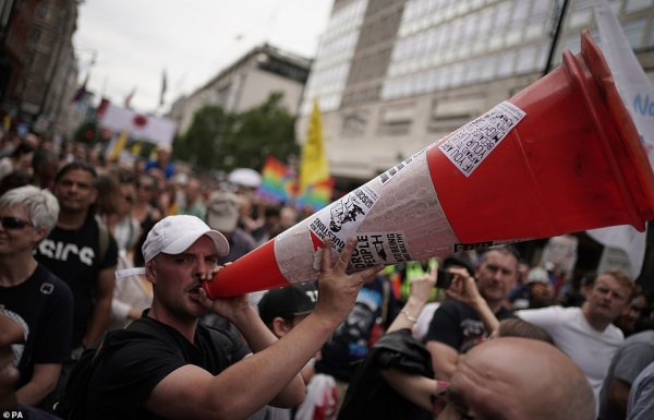 One protestor brandished a traffic cone as a makeshift megaphone as tens of thousands marched through central London on Saturday