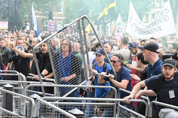 Tensions appeared to increase outside Downing Street as anti-lockdown protesters threw the fencing blocking them from the police officers who stood in a line on the other side