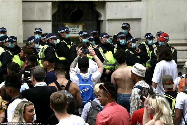 A crowd of police officers created a barrier as swathes of demonstrators looked on in London earlier this afternoon
