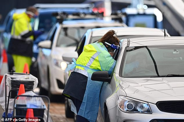 A health workers at the Bondi drive-thru clinic performs a swab test (pictured on Sunday) as the Bondi cluster grew to 110 cases, with two more mystery cases lingering in Sydney