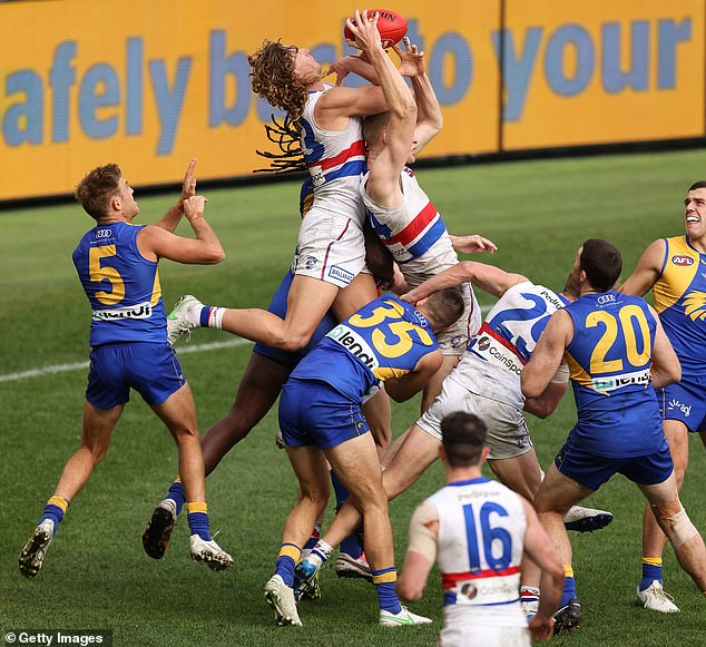 Players at Optus Stadium leap for the ball with nobody in the stands watching on (pictured on Sunday) after WA brought in a string of restrictions