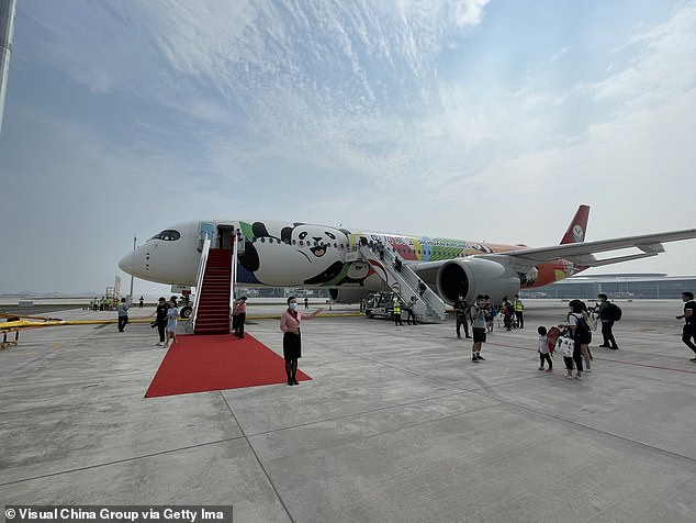 Passengers prepare to board the first plane to depart from the new airport, one of 160 China plans to build in the next 14 years