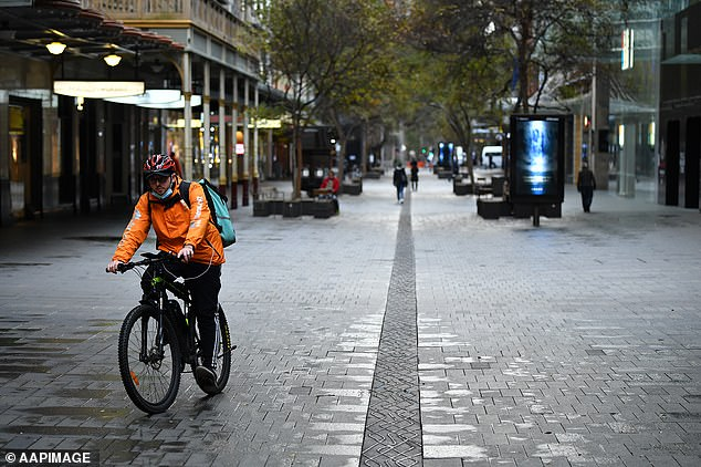 A food delivery cyclist rides down a deserted shopping street in Sydney on Monday amid new lockdown measures