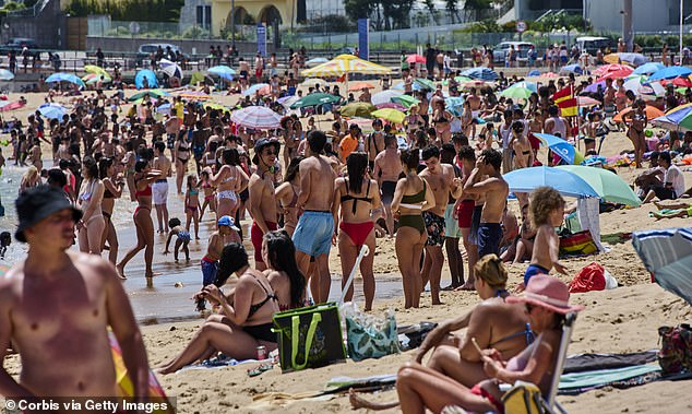Beachgoers crowd Santo Amaro beach near Lisbon on a hot and sunny afternoon in Portugal's Day holiday during COVID-19 Coronavirus pandemic on June 10