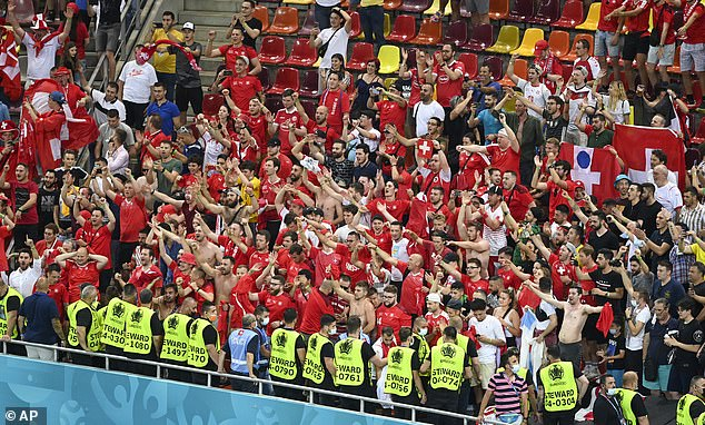 Pictured: Swiss fans celebrate inBucharest after watching their team come back from 3-1 down against tournament favourites France to win on penalties