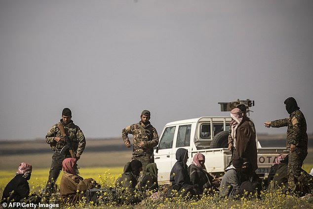 Surrendering suspected ISIS members sit on the ground as US-backed Syrian Democratic Forces troops take them prisoner