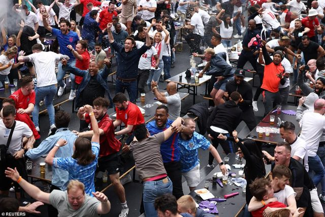 Celebrations where friends embraced each other were pictured across the country. (Above: Three Lions supporters celebrate the victory at Boxpark in Croydon, London)