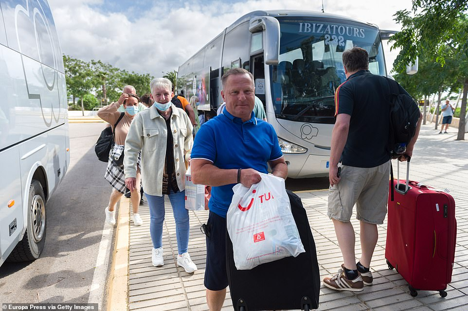On Thursday, UK Transport Grant Shapps announced that Mallorca, Ibiza and Menorca - along with Madeira, Grenada, Barbados and Bermuda - have all been added to the green list after being downgraded from amber. Pictured: British tourists wait for a bus at Ibiza Airport on Wednesday