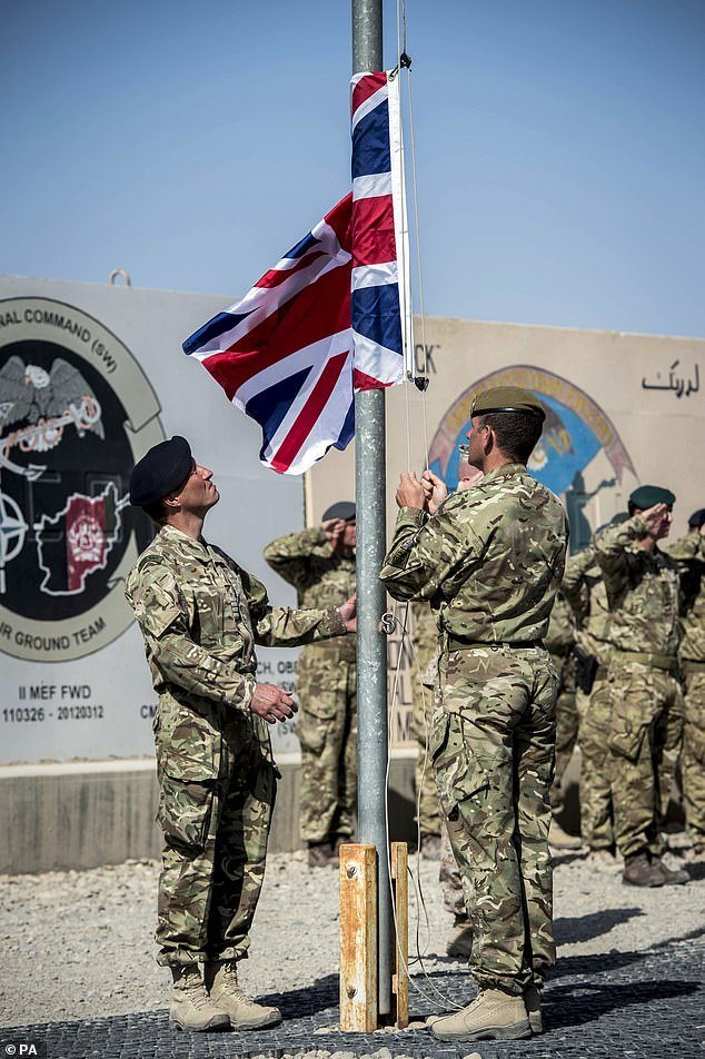 The last Union flag of Great Britain flying above the skies of Helmand Province, Afghanistan, is lowered by Captain Matthew Clark andWarrant Officer 1 John Lilley to be returned to the UK