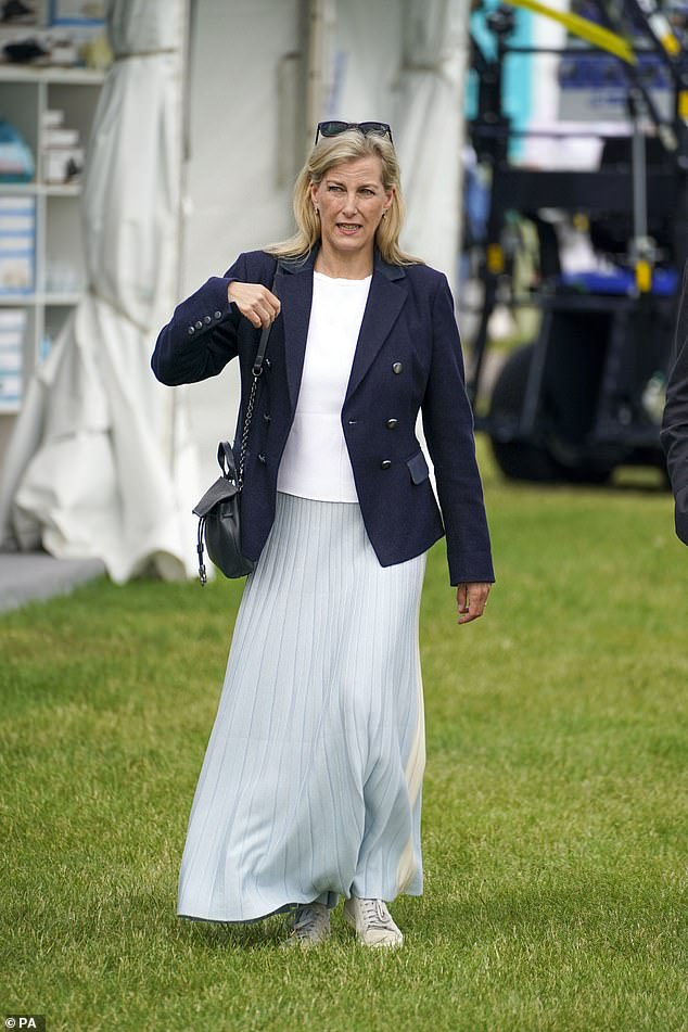 She swapped her usual heels for a pair of sensible, white trainers as she strolled through the grounds across the grass and chatted with other attendees