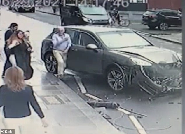 This is the terrifying moment a Porsche veered across the wrong side of the road, missing a pedestrian and a cyclist by inches (the driver getting out of the car after the crash, pictured)
