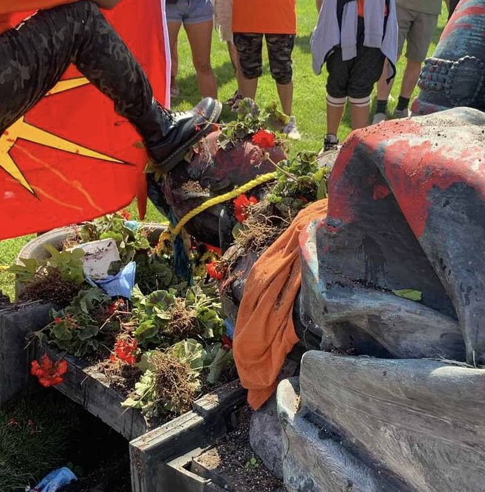 One protester places a boot on Queen Victoria's toppled statue in Winnipeg