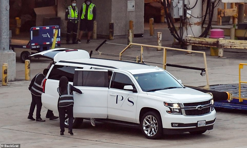 Airport workers open the car door as they let the Prince out after his flight form Heathrow back to Los Angeles this morning